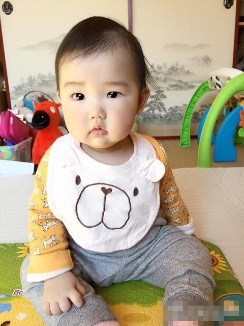 """""""照片中,小宝宝坐在床上,小脸肉嘟嘟的,双眼圆溜溜亮晶晶,十分可爱."""