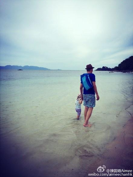 父子两手牵手在海边踏浪