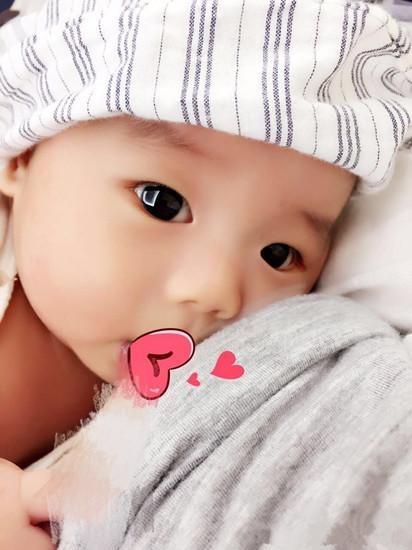 婴儿帽斜躺在黄英怀里,圆润的小脸颊上还能看到淡淡红晕,乖萌可爱的样