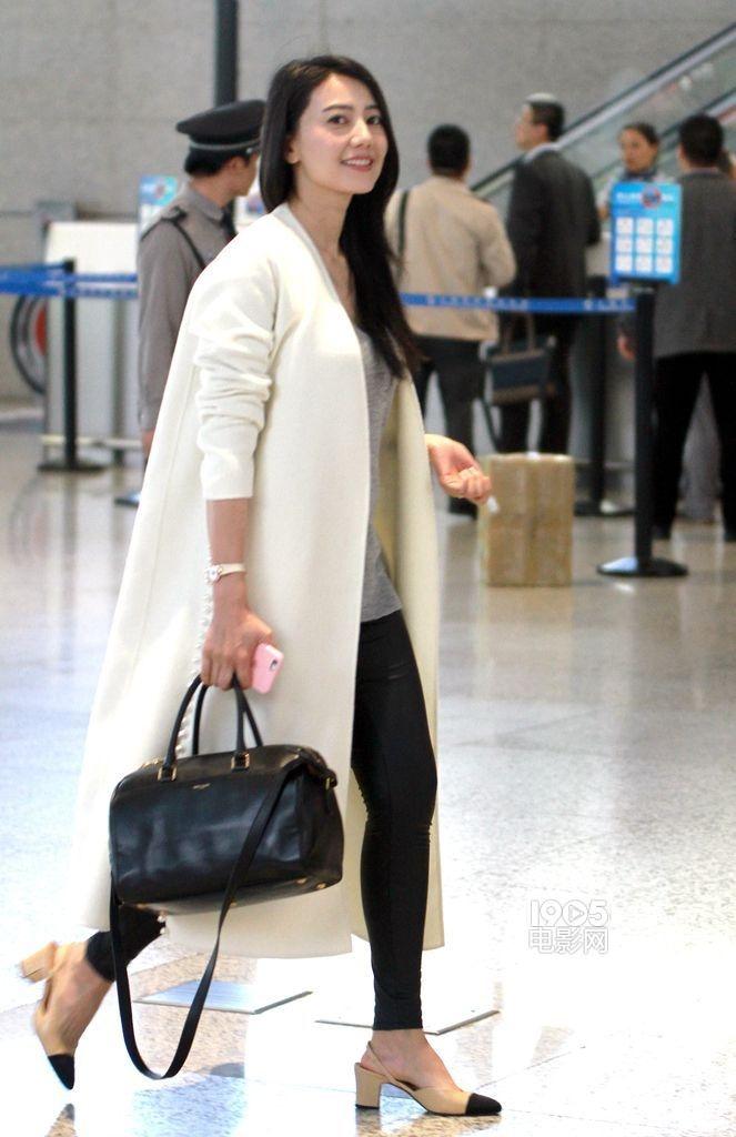 """高圆圆穿白色大衣机场""""走秀"""" 甜笑显女神范儿"""