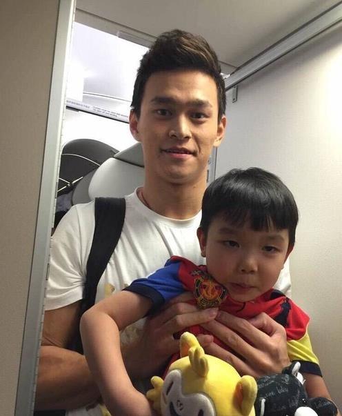 照片里的孙杨穿着白t很是精神,小男孩也对着镜头嘟嘴,十分可爱.