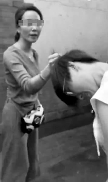 骑车女子(左)揪住刘女士头发。 视频截图