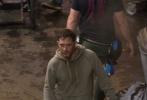 """2017年11月3日,美国亚特兰大,《蜘蛛侠》的外传电影《毒液》拍摄进入第三个星期,曝出了最新的片场照。""""汤老师""""汤姆·哈迪一身运动帽衫,脸上似乎还有擦伤,造型狼狈颓废。他对着空气飙戏超级投入,表情到位。一段表演结束后,他一边和导演探讨剧情,一边拿起电子烟吞云吐雾。之后他脱下灰色帽衫,露出一身结实的肌肉,臂膀上的纹身清晰可见。"""